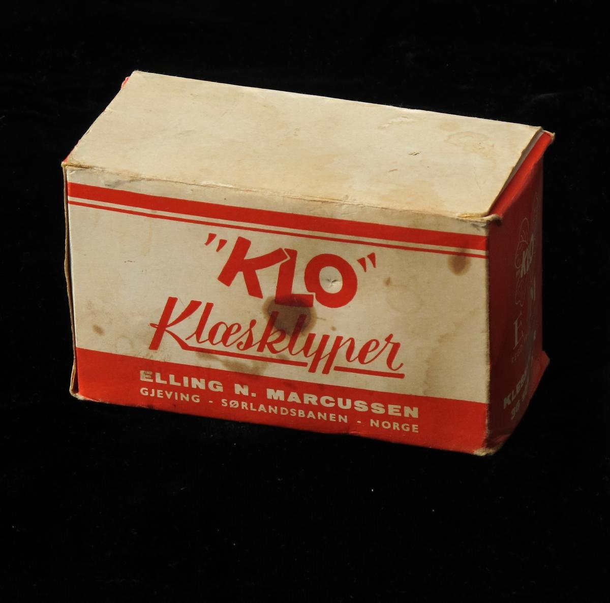 Eske av kartong, trykk i rød farge. Esken inneholder 36 klesklyper av tre.