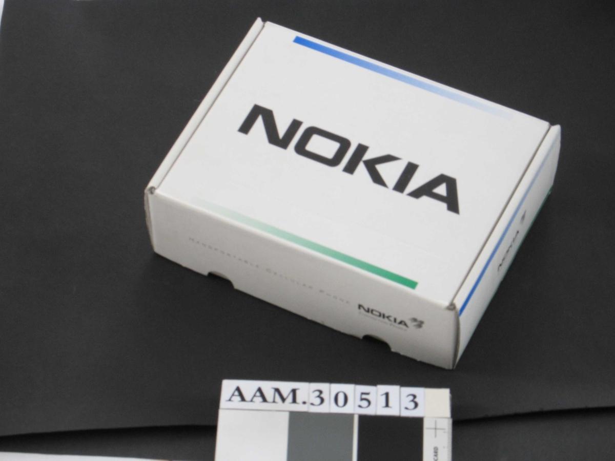 Rektangulær, med liten antenne.  Telefonen (AAM.30513.A) ligger i eske (AAM.30513.B), sammen med tilhørende bruksanvisninger og brev vedrørende abonnement. Den første mobiltelefonen til Aust-Agder museumstjeneste.