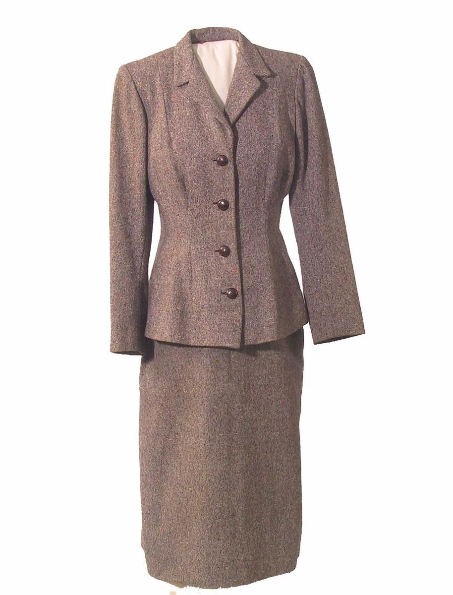 Jakke av tweed med for av kunstsilke (?) og knapper av skinnimitasjon. Innsvinget jakke med krage og slag, 4 knapper midt foran, skulderputer, 2 pynteknapper ved hvert håndledd.