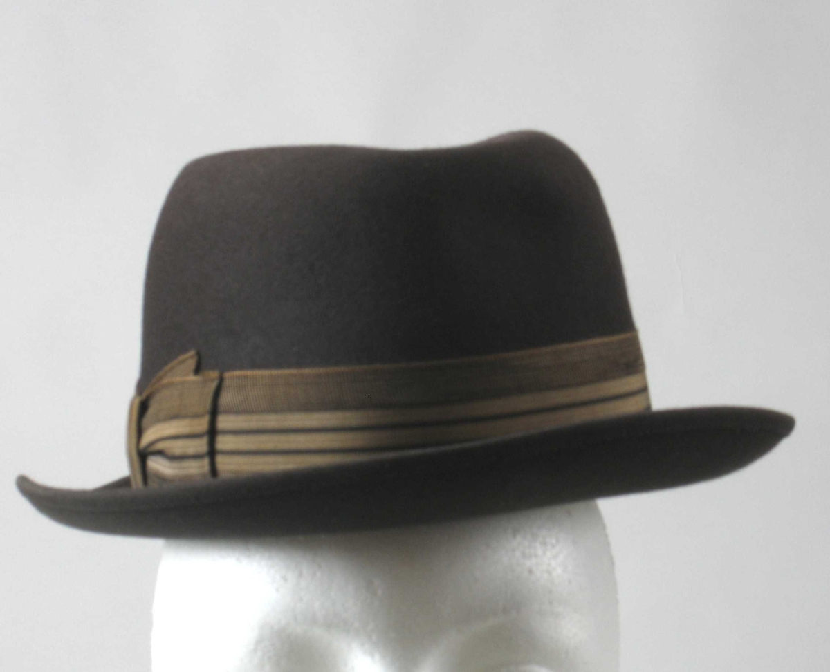 Form: Pull trykt ned på toppen og på hver side øverst foran. Bremmen vippet opp bak. Stripet hattebånd med endene sydd fast som flat sløyfe på den ene siden.