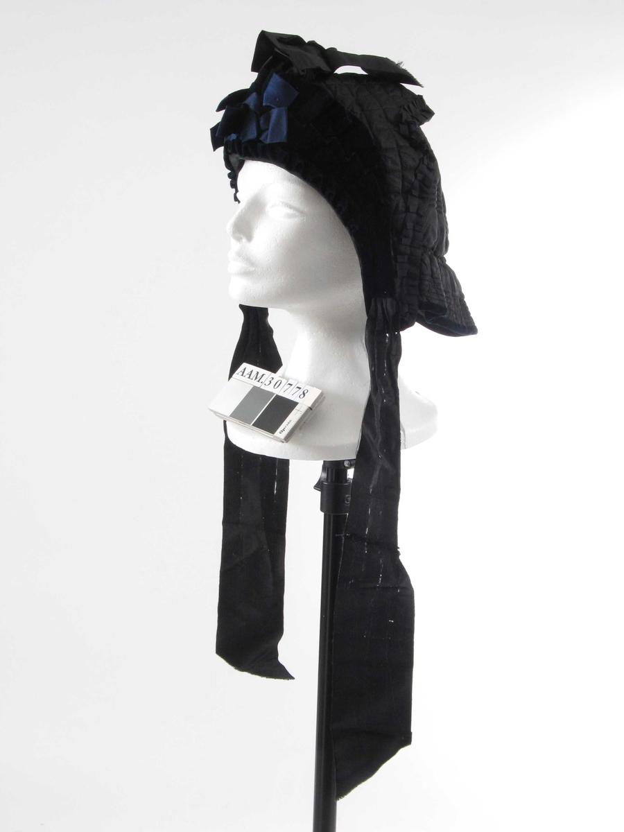 Myk og vattert hatt, består av 2 lag. Det innerste går helt til skuldre, har kappe nederst og er formet i spiss midt bak. Pyntet med sløyfer, knyttes med bånd.
