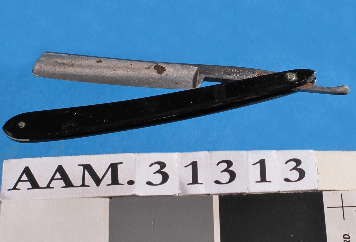 a) Foldbar barberkniv.  Stålblad.  Svart bakelitt-håndtak bestående av to tynne lett buede plater som bladet folder inn mellom.  To stifter (en i hver ende).  Den ene stiften holder bladet, den andre holder en liten trekantet hvit plate, som holder kaftedelene fra hverandre og hindrer at bladet går tvers gjennom skaftet. b) Plastetui som opprinnelig er laget til en saks, men som kniven var oppbevart i.  Bakside rød plast, frorside klar plast.  Den klare forsiden er forlenget slik at den kan stikkes som en klaff ned under en rød plastremse som er sveisa bakpå.  På den røde baksiden er det stemplet inn H.Eicker u. Söhne (over) Solingen - W. (over) Germany.  Sannsynligvis sakseprodusenten.