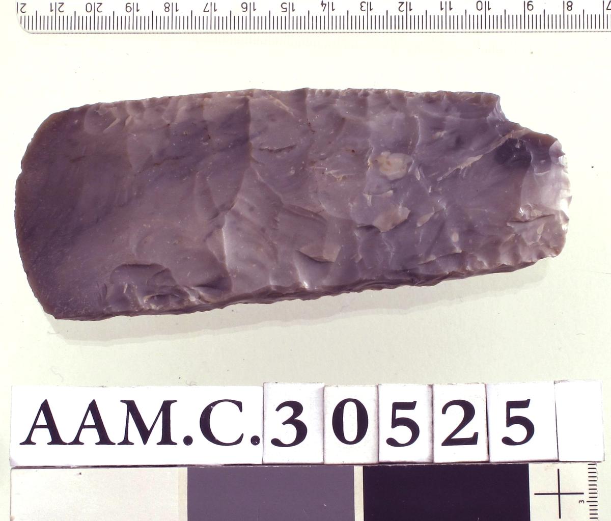 Tykknakket, tynnbladet øks av lys grå flint nærmest som E. Hinsch: B.M.Å. 1954, Hist. ant. rekke, nr. 1, fig. 84 b, men bare den ene bredsiden hvelvet. På den andre siden, som er flat, sitter en del av kalkskorpen igjen. Kun eggen slipt. Pent hugget. Et skall avslått ved nakken, ellers godt bevart.Lengde 13,8 cm, bredde over eggen 5,7 cm.