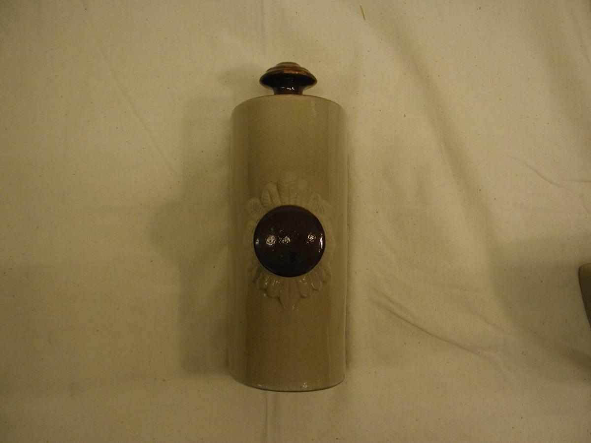 Flasken har en flat side og en hvelvet side med åpning for påfylling av varmt vann og kork. Rundt påningen er det formet en blomst. Den ene kortsiden er uten glasur, den andre har et knoppformet håndtak. Denne siden har brun glasur.