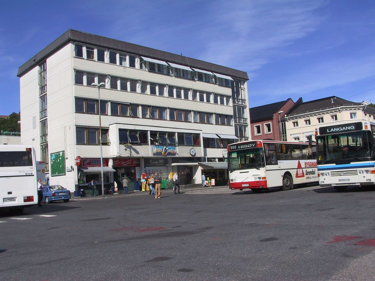 Rutebilstasjonen i Arendal, bygningen i bakgrunnen, busser til venstre og til høyre.