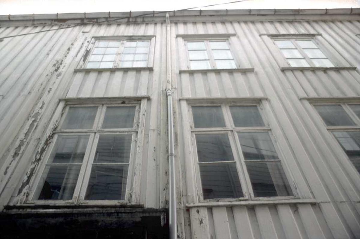 Arkitekturdetalj, Løvolds hus. Nordfasade  m. panel og vinduer, fotografert oppover mot gesims.