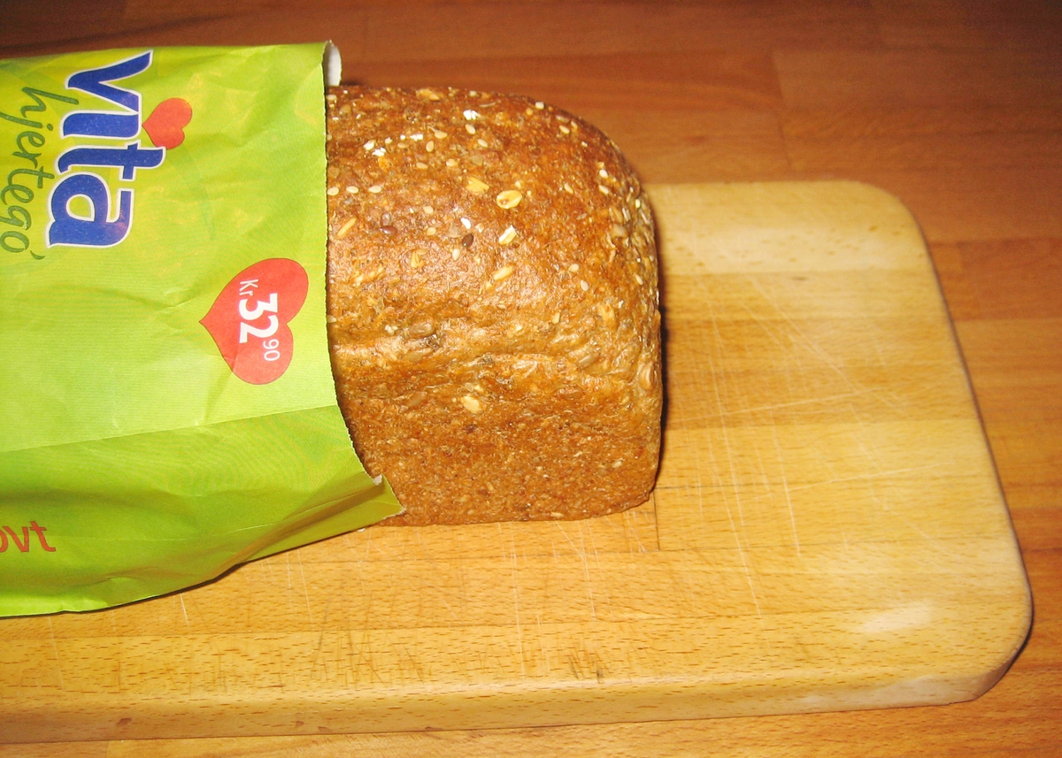 Motivet på brødposens forside er oppskåret brød. Foran brødet ligger to brødskiver og et smørebrød med salat, pålegg, tomat, asparges og persille. Brød og brødskiver er plassert på en trebenkeplate.