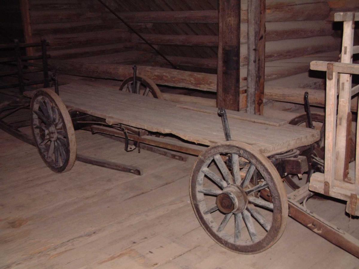 Understell bestående av bakvogn og framvogn med svingflak. Akslingene er forbundet med mellomstang. Jernbeslåtte trehjul med svak styrt. Løs lem som er typisk for denne typen vogner. Fire løse keipestaker. Originalt drag.
