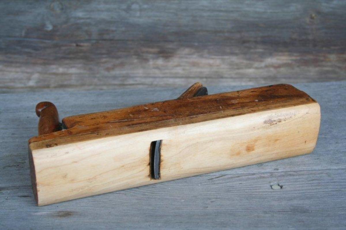 Høvelstokk i to deler. Nedre del er i et annet treslag og har lett avrundet såle. Høvelernet er avrundet i underkant. Liten, dekorativ vulst øverst på høvelhornet.