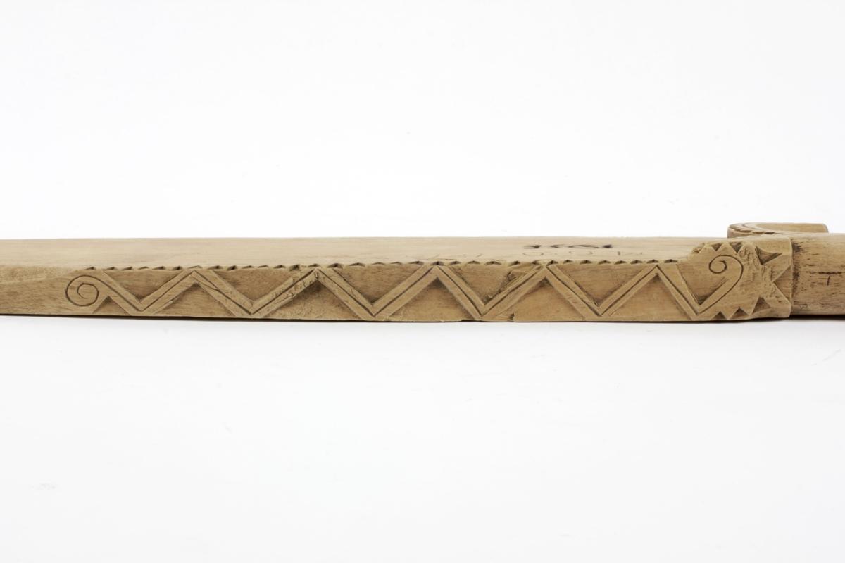 Tannsnitt og trekanter på oversiden og tannsnitt langs kanten ved håndtaket, blomst risset inn ved håndtaket