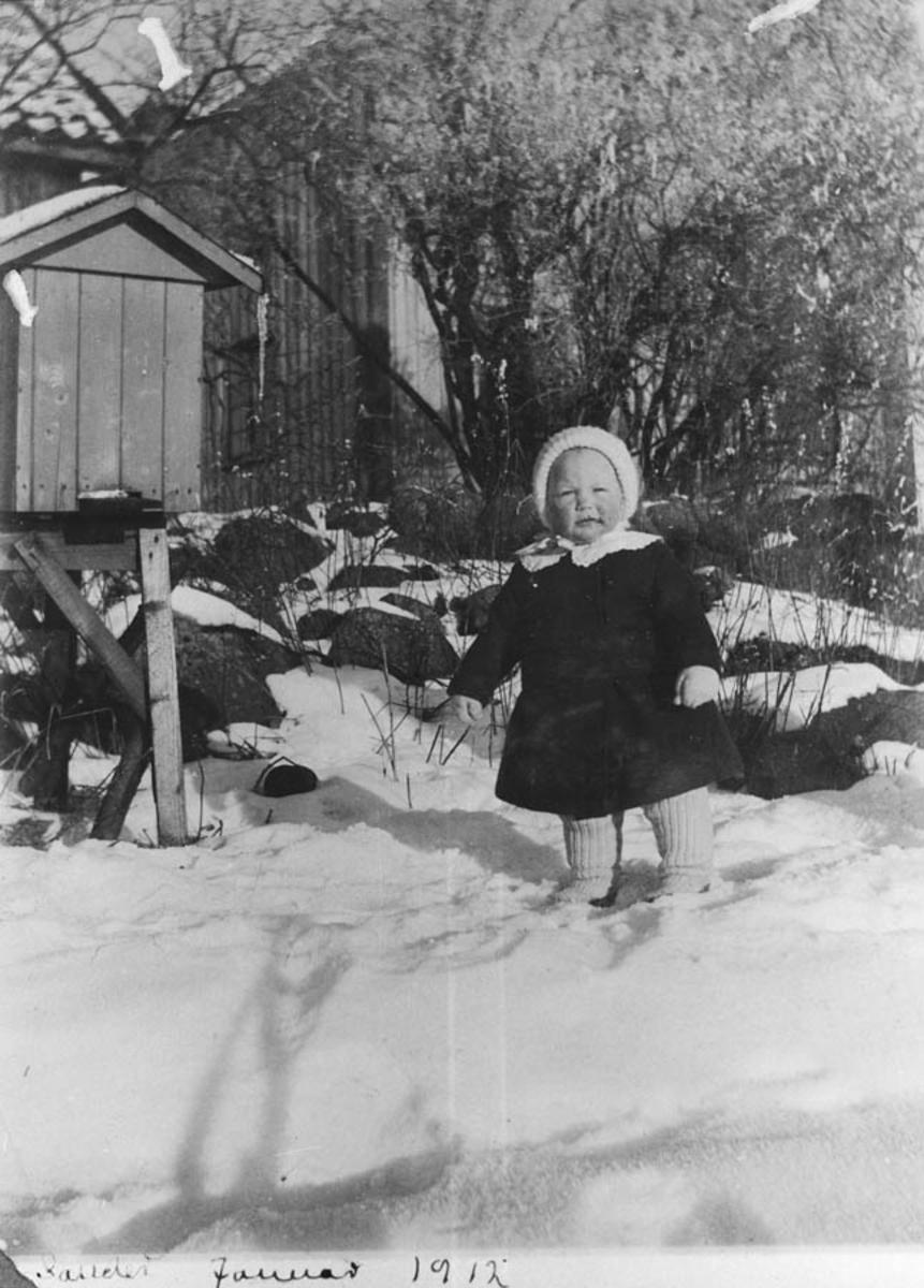 Ellen 1 år ute i sneen med kåpe på.