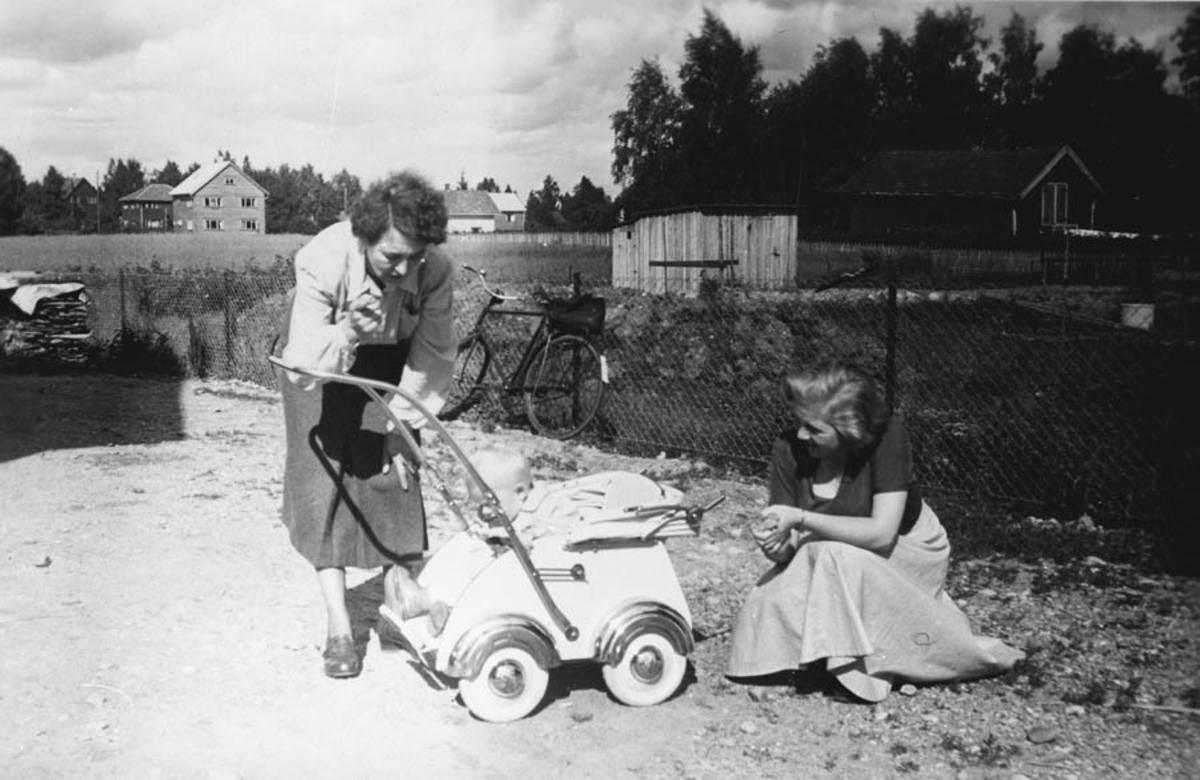 Gruppebilde. To damer og en barnevogn.