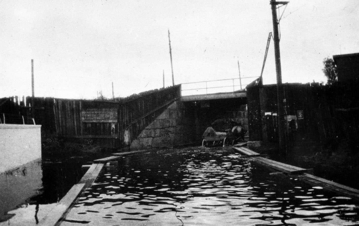 Jernbaneundergang i Lillestrøm under (regnværs?)flom 1910. På begge sider av veien ligger flåteganger. En hest med trille vader gjennom undergangen. Vannet når omtrent til akslingen på trilla.