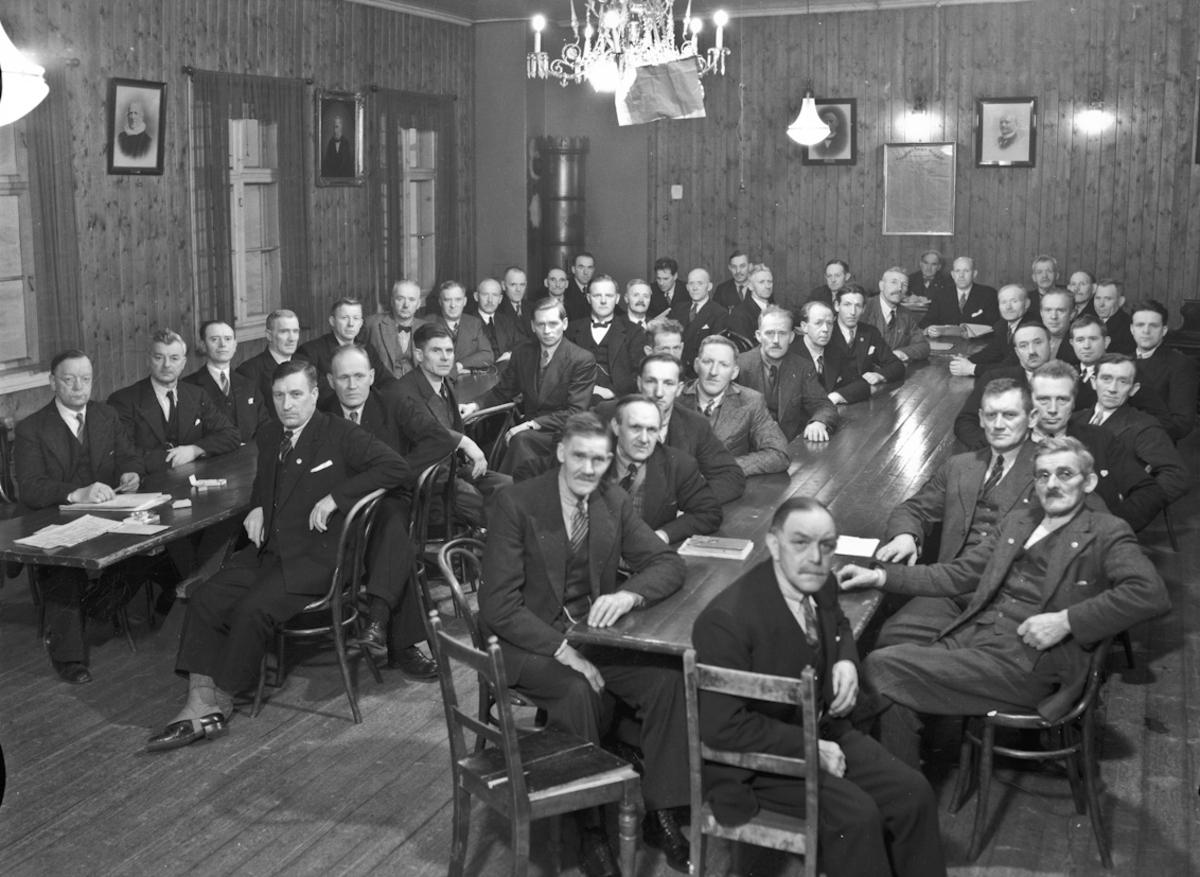 Forsamling menn. Bilder av gamle ordførere på veggen. Så da er det kanskje en politisk forsamling? Jens Røkholt på bildet.