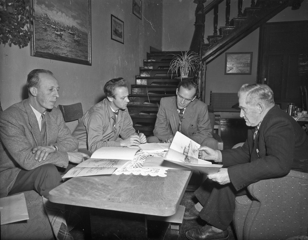 4 menn studerer papirer som kan se ut som byggetegninger. Erling Østerud til høyre(?). Kan være byggeprosjekt på Romerike Fylkesskole/Folkesskole.