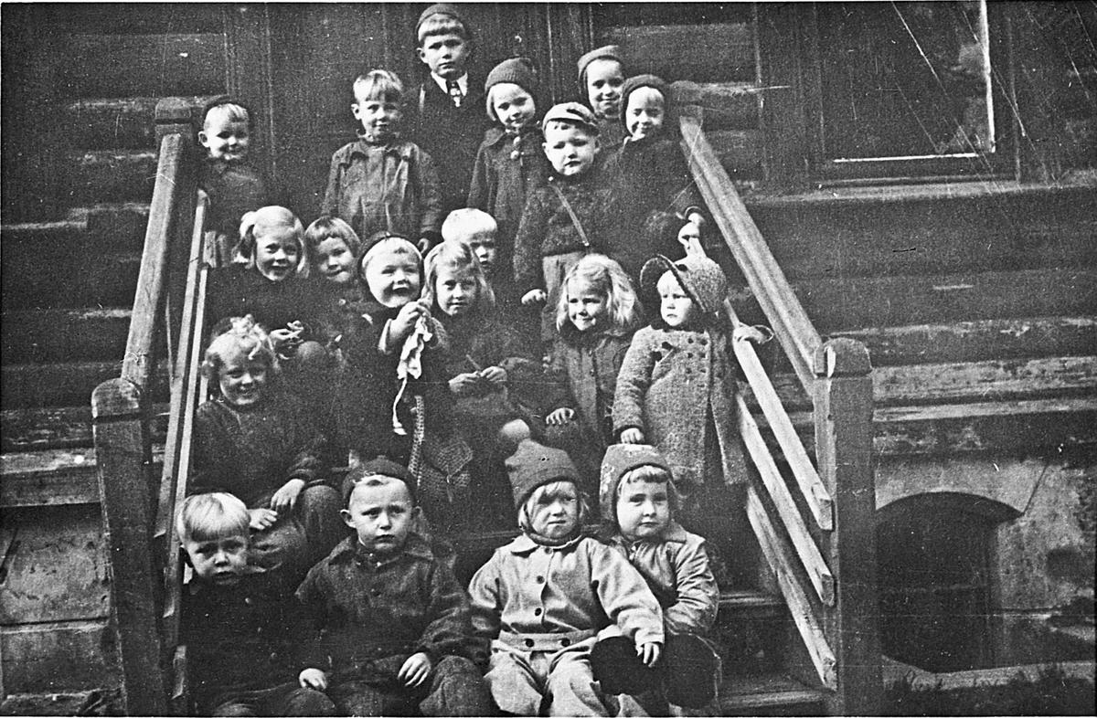 """Fra barnehagen """"Lerkelund"""" på Bøn. 1948. Barnehagen ble drevet av Mathiesen fram til 1964, hovedsakelig for barn til ansatte hos MEV, men også en del andre. Fremste rad fra v.: Per Halfdan Walstad, Finn Haugen, Liss Ekeland, Mary Sønstevold(?). Andre rad fra v.: May Bjerke. Tredje rad fra v.: Aud Sundt, X, Jan Henrik Jenssen, X, Åge Ruud (delvis skjult), X, Mari-Ann Karlsen. Bakerste rad: Ove Gran, X, Roald Haugen, Randi Kristiansen, Kjell Hanssen, Else Fredriksen, X. 07.04.2014: Denne kommentaren har et kartkoordinat angitt (lat/long): 60.290059,11.207045 Skrevet av: Peter"""