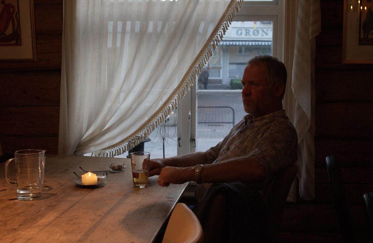 Mann med sigarett ved et bord, Jungeltelegrafen, Drøbak.