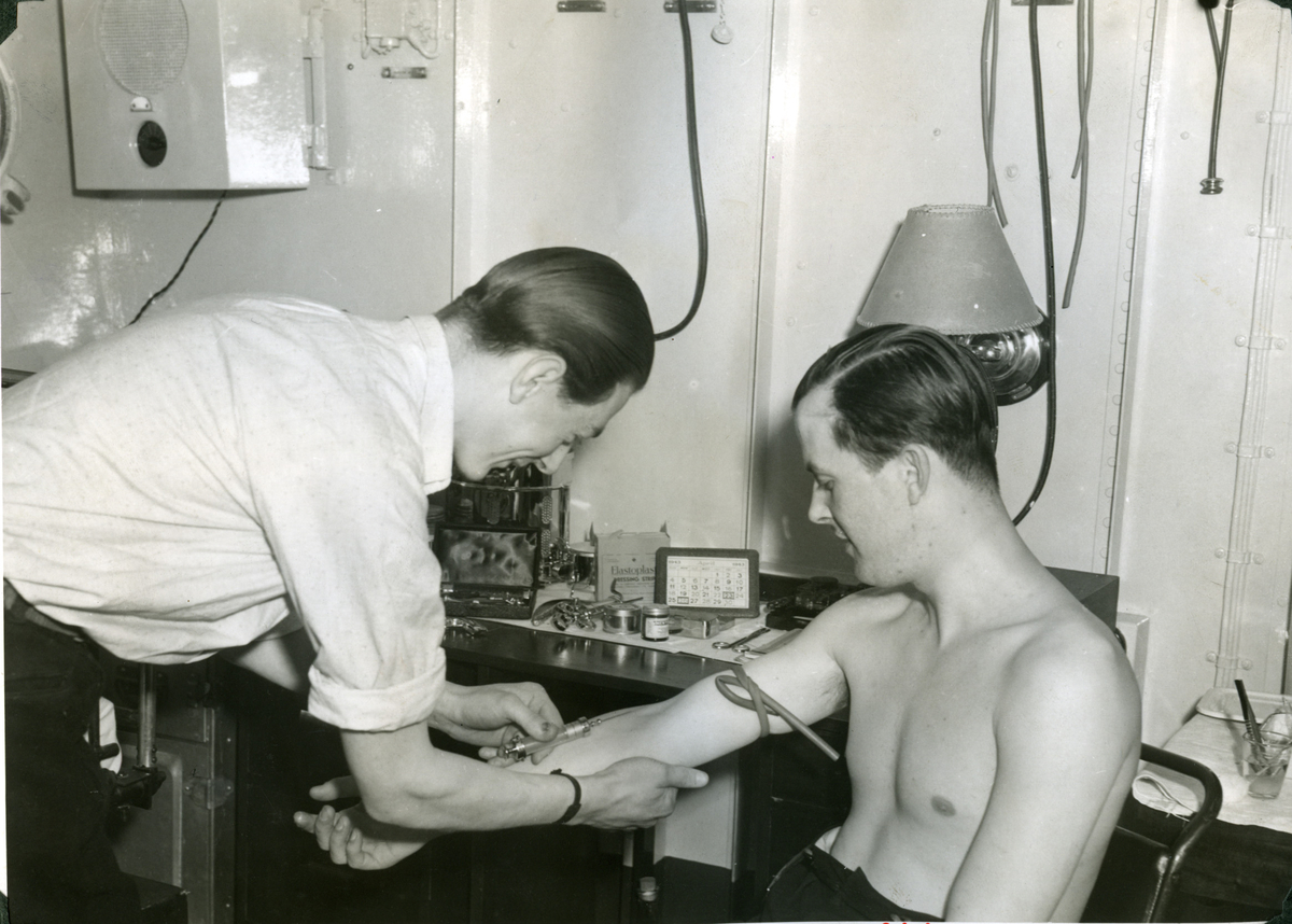 """Album Glaisdale H.Nor.M.S. """"Glaisdale"""". Fotograf: Ìnformation office. Noen av mannskapet gjennomgår medisinsk undersøkelse."""