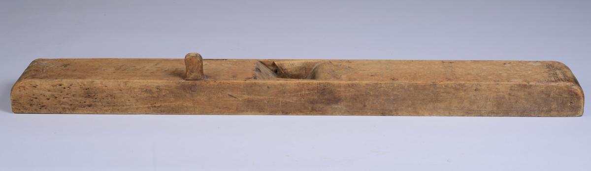 Avlangt rektangulært redskap med en isatt knott for håndtak. Åpning i bredden for å sette i knivblad. Enkel symetrisk dekor ved denne åpningen.