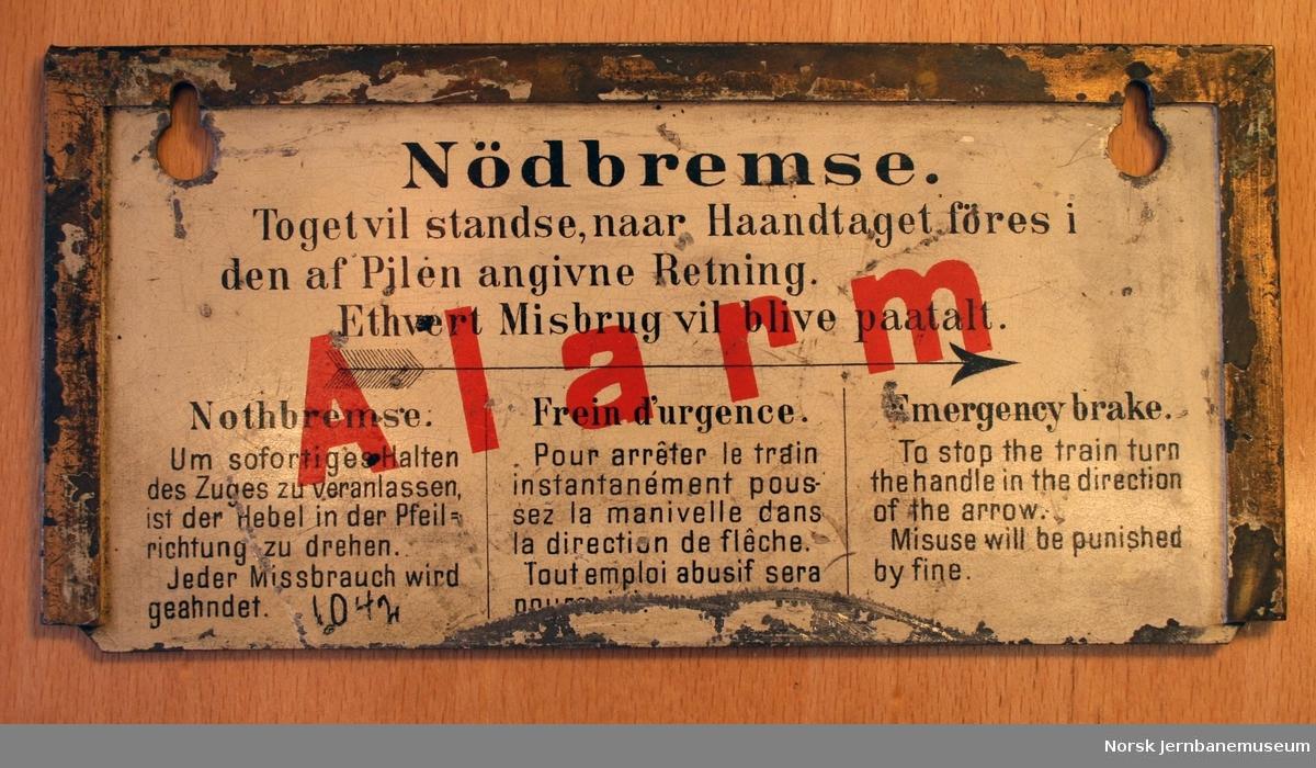 Skilt med informasjon om nødbremse. På en side tekst om line under takgesimset, på den andre siden om håndtak (tre språk).